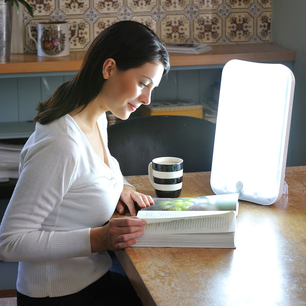 sad light therapy lamp with lux being used while reading. Black Bedroom Furniture Sets. Home Design Ideas