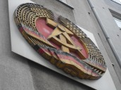 """The National Emblem of the German Democratic Republic: A hammer and compass, surrounded by a ring of rye, in Germany's colours black, red and gold. Emblem on the side of the """"House at Checkpoint Charlie"""". Photo: Cornelia Kaufmann"""