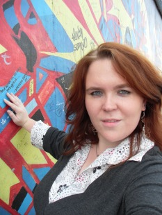 I'm touching a remnant of the Berlin Wall. Until 1989, I could have been killed for getting this close to the Wall. Photo taken at East Side Gallery, Berlin. Photo: Cornelia Kaufmann