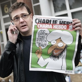 "Charb with a copy of the ""Charia Hebdo"" edition in 2011"