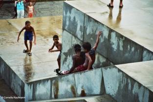 Children playing on the rain-soaked steps of El Capitolio. Copyright Cornelia Kaufmann