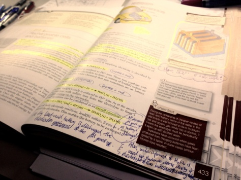 Annotated text book with highlighted text and margin notes.
