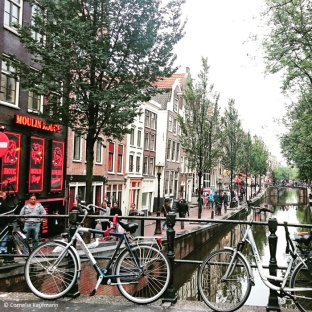 Bikes leaning against a bridge over a canal in Amsterdam's Red Light District De Wallen. © Cornelia Kaufmann
