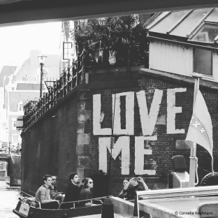 Love Me graffiti along the side of a canal in Amsterdam. © Cornelia Kaufmann