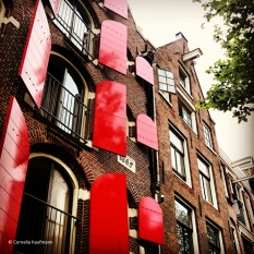 Red shutters on a building from the 17th century in Amsterdam's Red Light District. © Cornelia Kaufmann